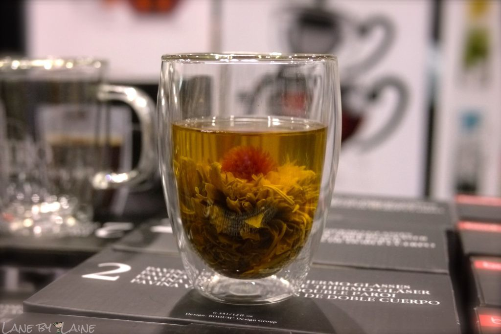 A flower tea ball blooms in a glass cup